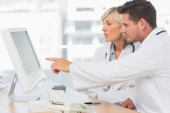 Doctors using computer at medical office Stock Photo