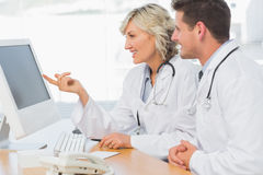 Doctors using computer at medical office Royalty Free Stock Photos