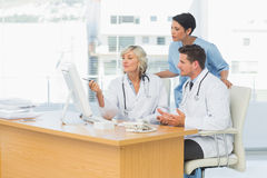 Doctors using computer together at medical office Stock Photos