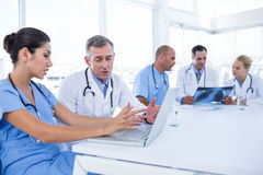 Doctors using computer whiles theirs colleagues looking at Xray Stock Photos
