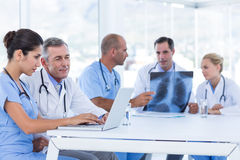 Doctors using computer whiles theirs colleagues looking at Xray Royalty Free Stock Images