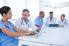 Doctors using computer whiles theirs colleagues looking at Xray Royalty Free Stock Photos