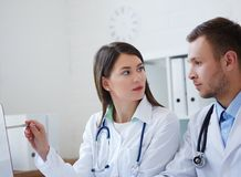 Doctors using desktop computer while discussing new way of treatment. Photo of two doctors together discussing new way of treatment while having a meeting at Stock Photography