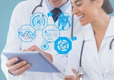 Doctors using digital tablet with multiple models interface in clinic. Smiling doctors using digital tablet with multiple models interface in clinic Royalty Free Stock Image