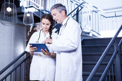 Doctors using digital tablet on staircase Royalty Free Stock Photos