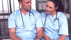 Doctors using laptop while sitting on floor stock video footage