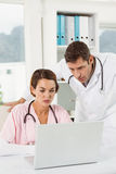 Doctors using laptop together at medical office Royalty Free Stock Images