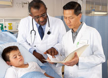 Doctors Visiting Child Patient On Ward Royalty Free Stock Photo