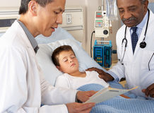 Doctors Visiting Child Patient On Ward Stock Image