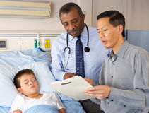Doctors Visiting Child Patient On Ward Royalty Free Stock Images