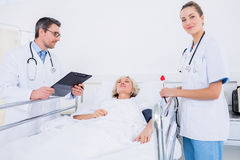 Doctors visiting a female patient in hospital Royalty Free Stock Photo