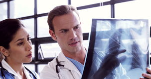 Doctors watching together a X-ray. In hospital stock footage