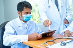 Free Doctors Wearing Protective Mask To Protect Against Covid-19 Use Tablets With Digital Of Technology Working In Clinic. Royalty Free Stock Photo - 183637415