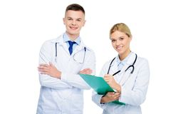 Doctors in white coats with diagnosis. Male and female doctors in white coats with stethoscopes and diagnosis, isolated on white stock photography