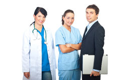 Doctors women and businessman. Two doctors women and a businessman with laptop standing in a row and smiling isolated on white background Stock Image