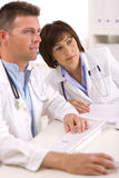 Doctors working at office. Medical doctors sitting at desk working at office royalty free stock image