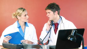 Doctors working in office and talking on phone stock footage