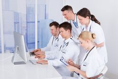 Doctors working together on computer in hospital Stock Photos