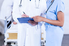 Doctors writing on clipboard. In hospital Royalty Free Stock Image