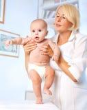 Doctrorpediater en baby. Eerste stappen Royalty-vrije Stock Foto's