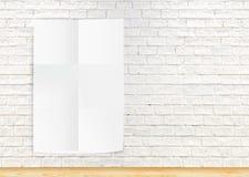 Document affiche die de witte bakstenen muur en de houten vloer hangen, te Royalty-vrije Stock Afbeeldingen