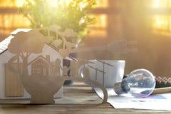 Document besnoeiing van eco op bureau Huismodel, lamp, pen, documentverhalen over energie - besparing, gelukkige families die sch stock foto