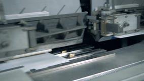 Document de dekking krijgt sticked aan de delen van een bewegende machine stock video