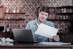 Document de examen de joyeux homme heureux image stock