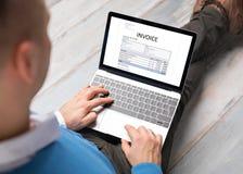Document de facture d'écriture d'homme sur l'ordinateur portable images stock