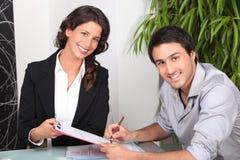 Document de signature de jeune homme et sourire de jeune femme Image libre de droits