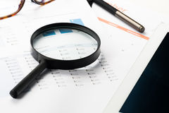 Document financial with magnifying glass.searching profit Royalty Free Stock Photos