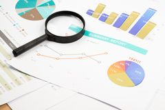Document financial with magnifying glass.searching profit. Stock Photography