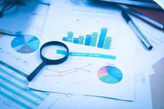 Document financial with magnifying glass Stock Images