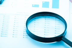 Document financial with magnifying glass.searching profit Royalty Free Stock Image