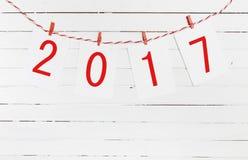 Document of fotokaders die met 2017 cijfers op de rode gestreepte kabel hangen Nieuw jaarontwerp Op houten achtergrond Stock Fotografie