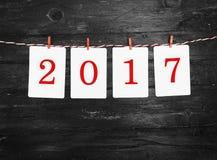 Document of fotokaders die met 2017 cijfers op de rode gestreepte kabel hangen Nieuw jaarontwerp Op houten achtergrond Stock Foto