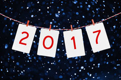 Document of fotokaders die met 2017 cijfers op de rode gestreepte kabel hangen Sneeuwvalachtergrond, Nieuw jaarontwerp Stock Afbeeldingen