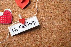 Document harten en nota met woorden KUNNEN WIJ HELPEN in bijlage aan koord op cork raad stock afbeelding