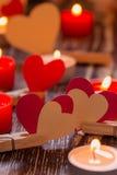 Document harten op wasknijpers en brandende kaarsen op houten tabl Stock Afbeelding