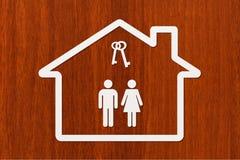 Document huis met binnen de mens, vrouw en sleutels Stock Fotografie