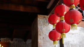 Document lantaarns bij de sjofele bouw Rode document lantaarns die op plafond van doorstane concrete tempel hangen die op zonnig  stock videobeelden