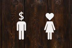 Document man dollarhoofd en vrouw met hart Liefde versus geldconcept Stock Afbeeldingen