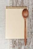 Document notitieboekje, houten lepel en linnenstof op het oude hout Stock Afbeeldingen