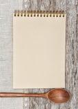 Document notitieboekje, houten lepel en linnenstof op het oude hout Stock Foto