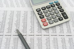 Document with numbers in several columns, calculator and pen Stock Image