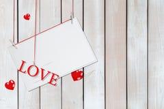 Document prentbriefkaar en woordliefde het hangen op rode draden die door harten met exemplaarruimte worden omringd op witte hout stock afbeeldingen