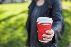 Document rood glas met een wit deksel en koffie in de handen van een meisje stock afbeelding