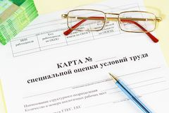 Document in Rus: Kaart van speciale beoordeling van arbeidsvoorwaarden, glazen, geld en een pen op de boekhoudingslijst stock foto