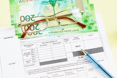 Document in Rus: Ontvangstbewijs voor betaling van nut Water, glazen, geld en een pen op de lijst stock afbeeldingen