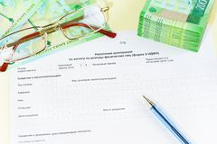 Document in Russian language of the Tax Declaration on the tax to incomes of physical persons form 3-NDFL. Points, money and pen on the table. Time to pay stock photography